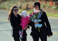 Residents arrive to pay tribute to the victims of an elementary school shooting in Newtown, Connecticut, on December 15, 2012. The US school gunman used an assault rifle to pump his mostly six- and seven-year old victims with multiple bullets, authorities said Saturday, as details of the horrific spree became clearer