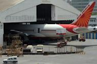 """An Air India passenger plane is parked at Chattrapati Shivaji International airport in Mumbai. At least 100 pilots from India's debt-laden national carrier Air India have failed to turn up to work on Tuesday in a move the civil aviation minister described as an """"illegal"""" strike"""