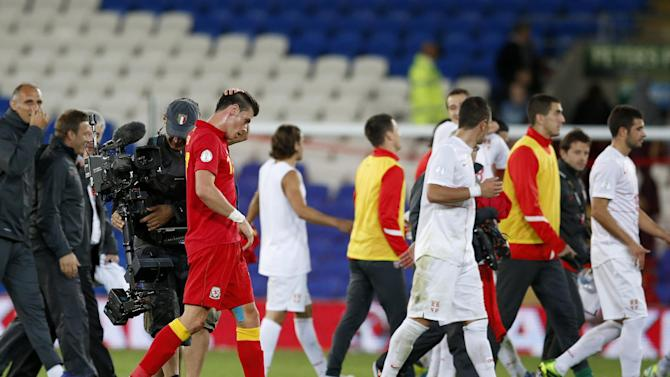 Wales' Gareth Bale, left, walks off at the end of their World Cup Group A qualifying soccer match against Serbia at Cardiff City Stadium in Cardiff, Wales, Tuesday, Sept. 10, 2013