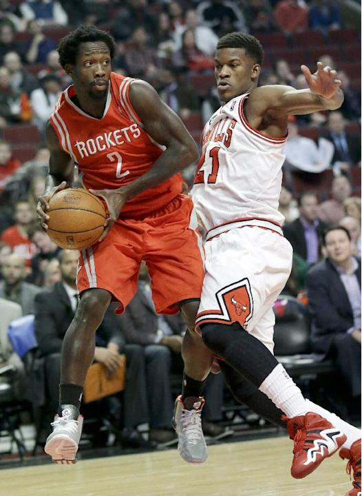 Houston Rockets guard Patrick Beverley, left, looks to pass as Chicago Bulls guard Jimmy Butler defends during the first half of an NBA basketball game in Chicago on Thursday, March 13, 2014