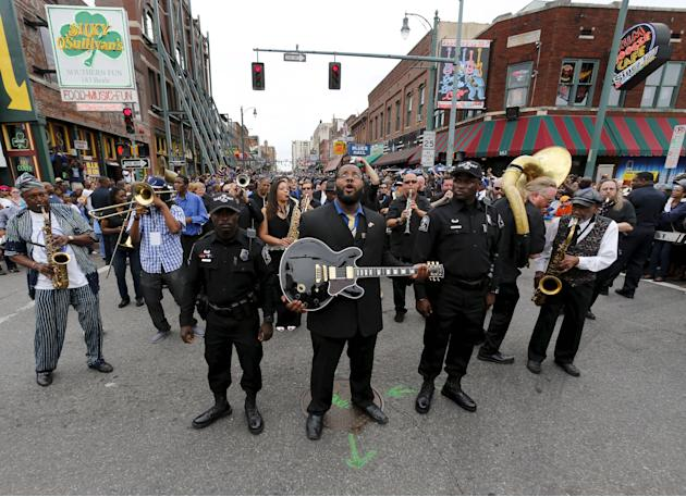 "Rodd Bland, son of Bobby ""Blue"" Bland, carries the iconic Gibson guitar named ""Lucille"" belonging to the late B.B. King during a procession down Beale Street in Memphis, Tennessee"