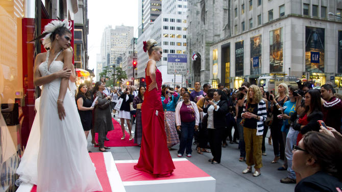 FILE - This Sept. 8, 2011 file photo shows models posing outside the Elizabeth Arden store on Fifth Avenue during Fashion's Night Out in New York. The annual shopping event has been part of New York Fashion Week each September since 2009, has been discontinued. Council of Fashion Designers of America CEO Steven Kolb said Wednesday, Feb. 27, 2013, that he was proud of what had been accomplished. However, there was grumbling from some stores and designers that it cost money they weren't sure they saw back in sales. Fashion's Night Out will still be held in select international cities.   (AP Photo/Charles Sykes, file)