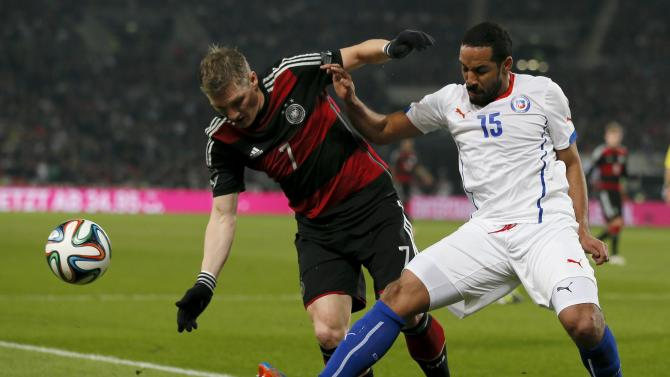 Germany's Schweinsteiger is tackled by Chile's Beausejour during their international friendly soccer match in Stuttgart