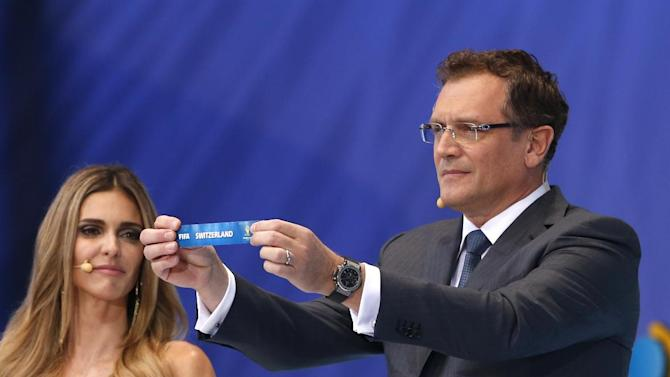 FIFA Secretary General Jerome Valcke shows the ticket of Switzerland during the draw ceremony for the 2014 soccer World Cup in Costa do Sauipe near Salvador, Brazil, Friday, Dec. 6, 2013