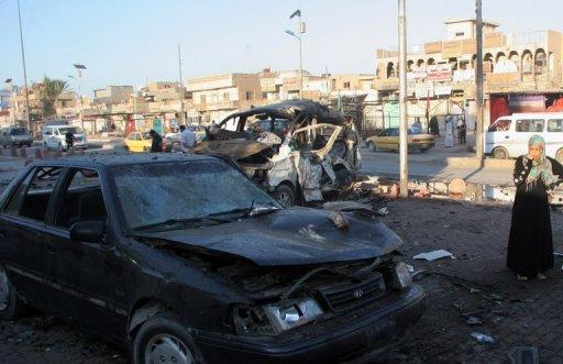 An Iraqi woman looks at the wreckage of destroyed cars on October 28 at the site of a car bomb that exploded the day before in Baghdad's Sadr city. A car bomb targeting Shiite pilgrims in Iraq killed three people and wounded 25 others on Saturday, during major Shiite religious commemorations, officials said