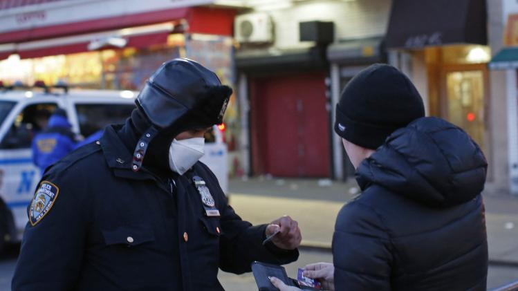 A New York Police officer checks the ID of a resident near the site of a building explosion in the Harlem section of New York