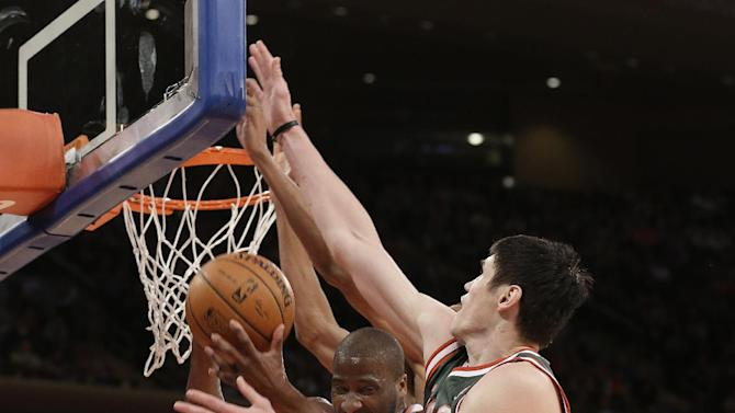 New York Knicks' Raymond Felton, center, and Milwaukee Bucks' Ersan Ilyasova, right, fight for a rebound during the first quarter of an NBA basketball game at New York's Madison Square Garden, Saturday, March 15, 2014