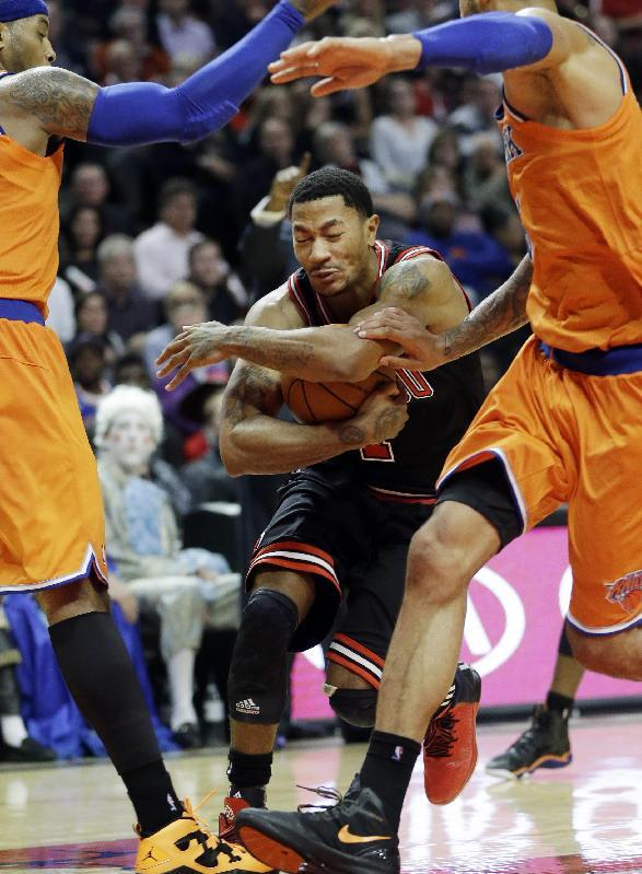Chicago Bulls guard Derrick Rose, center, drives to the basket between New York Knicks forward Carmelo Anthony, left, and center Tyson Chandler during the second half of an NBA basketball game in Chicago, Thursday, Oct. 31, 2013. The Bulls won 82-81