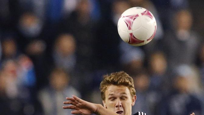 D.C. United midfielder Jared Jeffrey (25) heads the ball over Sporting KC midfielder Oriol Rosell, front, during the first half of an MLS soccer match in Kansas City, Kan., Friday, Oct. 18, 2013