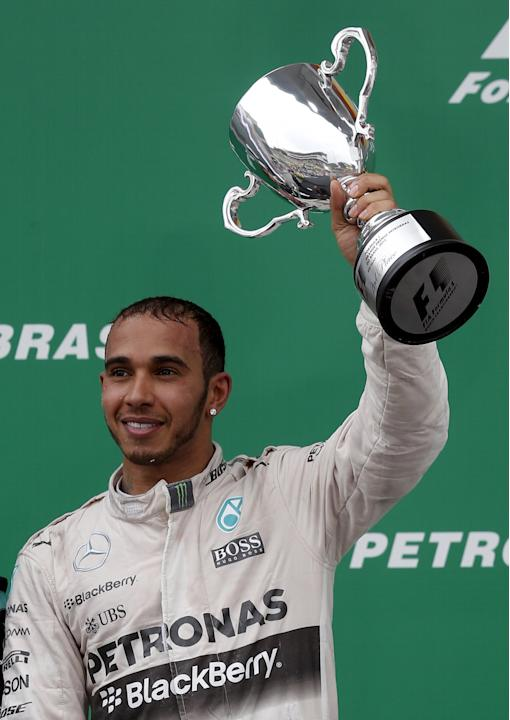 Hamilton of Britain raises his second place trophy after the Brazilian F1 Grand Prix in Sao Paulo