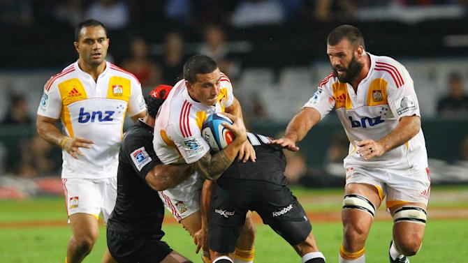 New Zealand Waikato Chiefs' Sonny Bill Williams (C) is tackled as teammates Alex Bradley (R) and Lelia Masaga (L) look at him during the Super 15 rugby union match Sharks of Durban vs Waikato Chiefs of New Zealand at the Mr Price Kings Park Rugby Stadium on April 21, 2012.   AFP PHOTO/ STR (Photo credit should read -/AFP/Getty Images)