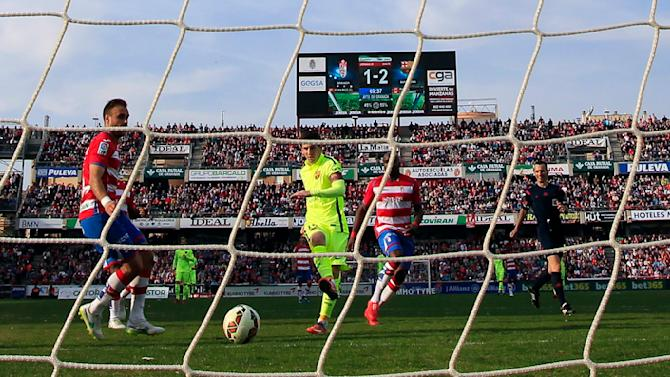 Barcelona's Lionel Messi (2nd L) scores a goal against Granada during their Spanish First Division soccer match at Nuevo Los Carmenes stadium in Granada