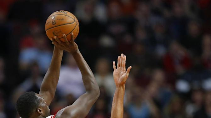 Chicago Bulls forward Luol Deng (9) shoots over Indiana Pacers guard George Hill during the first quarter of an NBA basketball game in Chicago, Saturday, Nov. 16, 2013