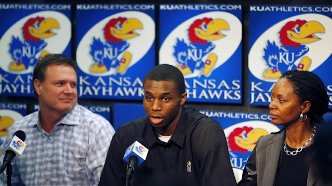 Kansas NCAA college freshman basketball player Andrew Wiggins, middle, speaks between coach Bill Self, left, and his mother Marita Payne-Wiggins, right, during a news conference at the University of Kansas in Lawrence, Kan., Monday, March 31, 2014. Wiggins announced he would be entering the NBA draft