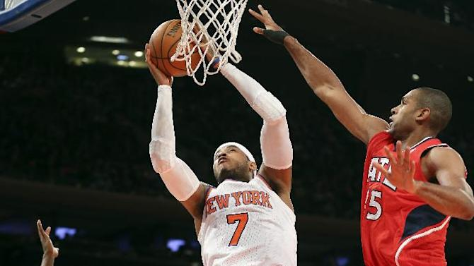 New York Knicks forward Carmelo Anthony (7) shoots against Atlanta Hawks forward DeMarre Carroll (5) as point guard Shelvin Mack (8) stands near during the first half of an NBA basketball game Saturday, Dec. 14, 2013, in New York