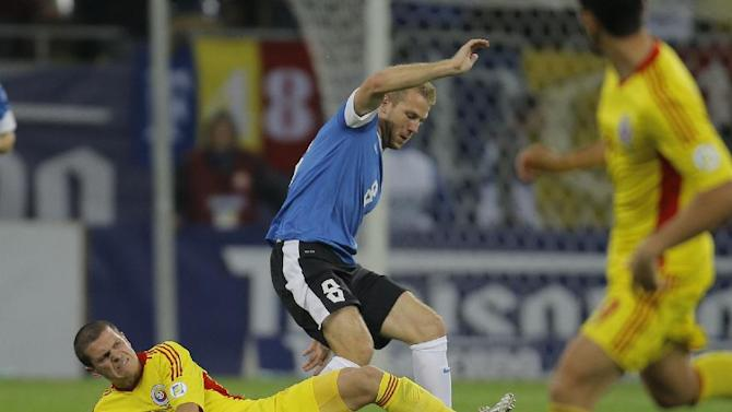 Henri Anier, centre top, of Estonia and Alexandru Bourceanu, left, of Romania control the ball during their World Cup Group D qualifying soccer match at the National Arena stadium in Bucharest, Romania, Tuesday, Oct. 15, 2013