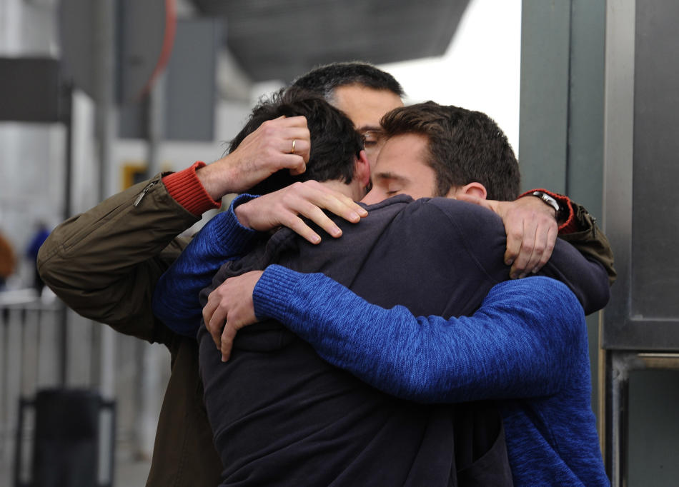 People comfort each other as they arrive at the Barcelona airport in Spain, Tuesday, March 24, 2015. A Germanwings passenger jet carrying 150 people crashed in the French Alps region as it traveled fr