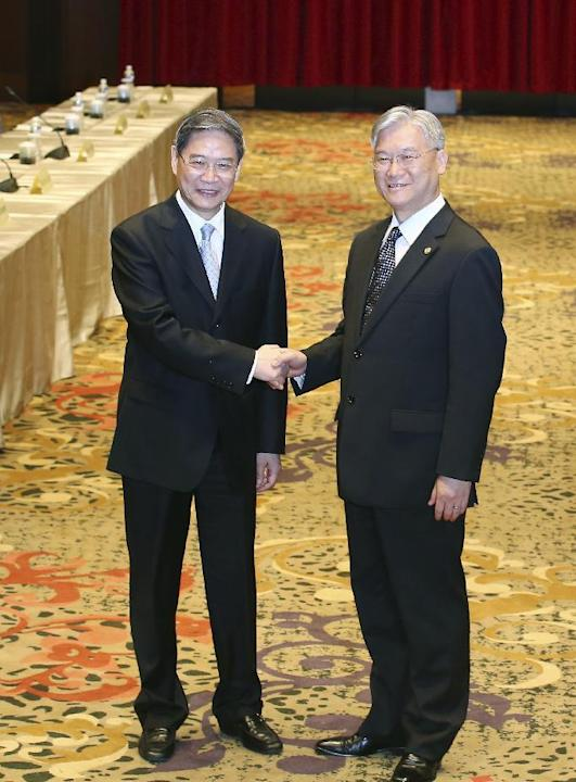 China's Taiwan Affairs Office director Zhang Zhijun, left, and his counterpart Minister Andrew Hsia of the Taiwan's Mainland Affairs Council shake hands in front of the media as they arrive fo