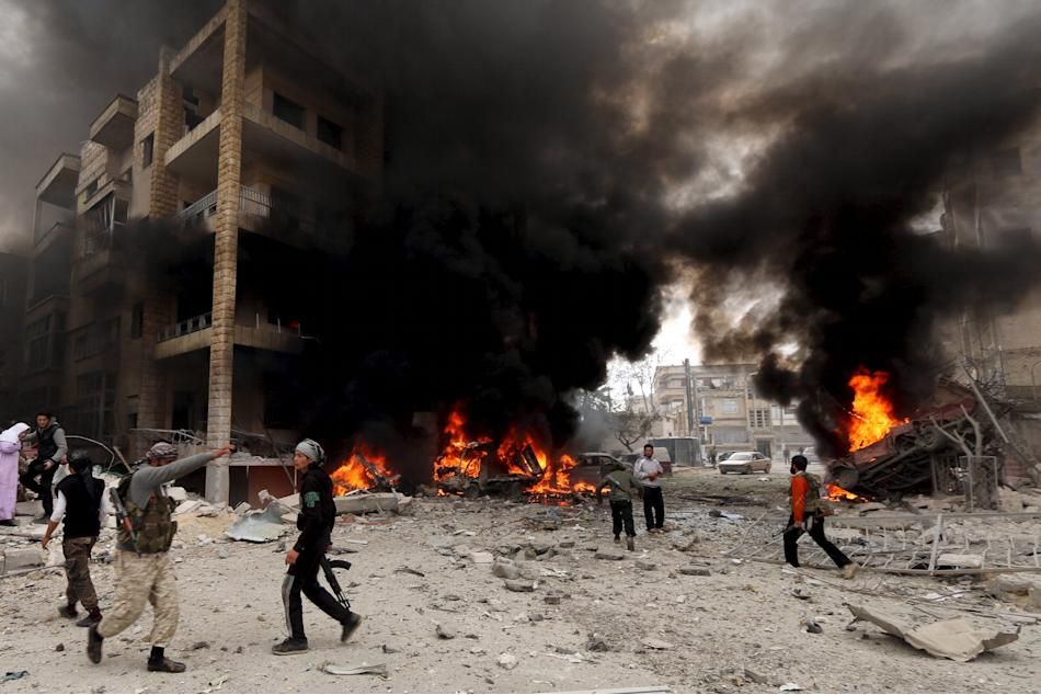 Residents and rebel fighters inspect fire at a damaged site after what activists said was shelling by forces loyal to Syria's president Bashar al-Assad on Al-Dubeit neighborhood in Idlib city