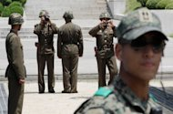 Photo illustration shows North Korean soldiers (background) and a South Korean Army soldier (R) standing guard at the border village of Panmunjom. A Seoul court on Tuesday awarded a fisherman compensation of more than $2 mn for being tortured and imprisoned in the 1980s on false charges of spying for the North