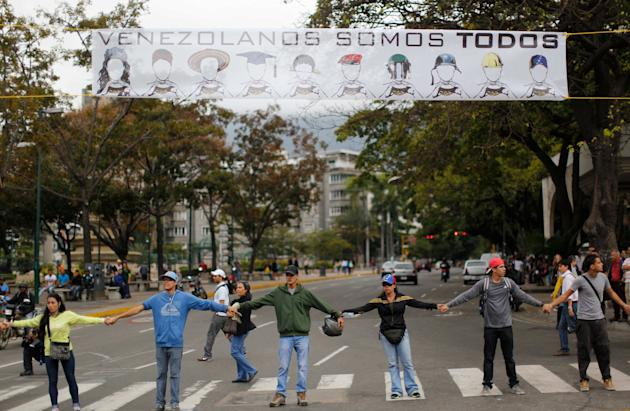 "Demonstrators join hands to block the highway at Altamira neighborhood in Caracas, Venezuela, Monday, Feb. 24, 2014. The banner over their heads reads in Spanish ""We are all Venezuela"". Traffic has co"
