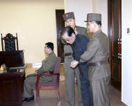 REFILE - CLARIFYING DATES Jang Song Thaek, with his hands tied with a rope, is dragged into the court by uniformed personnel December 12, 2013 in this picture published in Rodong Sinmun December 13, 2013 and released by Yonhap. North Korea said on Friday that Jang, the uncle of leader Kim Jong Un, previously considered the second most powerful man in the secretive state, has been executed for treason, the biggest upheaval since the death of Kim's father two years ago. REUTERS/Yonhap (NORTH KOREA - Tags: POLITICS MILITARY) ATTENTION EDITORS - THIS PICTURE WAS PROVIDED BY A THIRD PARTY. REUTERS IS UNABLE TO INDEPENDENTLY VERIFY THE AUTHENTICITY, CONTENT, LOCATION OR DATE OF THIS IMAGE. FOR EDITORIAL USE ONLY. NOT FOR SALE FOR MARKETING OR ADVERTISING CAMPAIGNS. NO SALES. NO ARCHIVES. THIS PICTURE IS DISTRIBUTED EXACTLY AS RECEIVED BY REUTERS, AS A SERVICE TO CLIENTS. NO THIRD PARTY SALES. NOT FOR USE BY REUTERS THIRD PARTY DISTRIBUTORS. SOUTH KOREA OUT. NO COMMERCIAL OR EDITORIAL SALES IN SOUTH KOREA