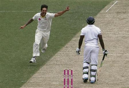 Australia's Mitchell Johnson (C) celebrates taking the wicket of England's Michael Carberry (R) for a duck during the first day of the fifth Ashes cricket test at the Sydney cricket ground January 3, 2014. REUTERS/David Gray