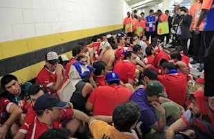 Chilean fans are surrounded by security personnel after breaking into Maracana Stadium. (AP)