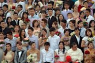 Newlywed couples pose for a group picture during a mass wedding ceremony in conjunction with the date 12/12/12 at a Chinese temple in Kuala Lumpur on December 12, 2012. Some 200 couples gathered at the temple to attend a grand colourful wedding ceremony on the date, which many in Asia mark as auspicious.