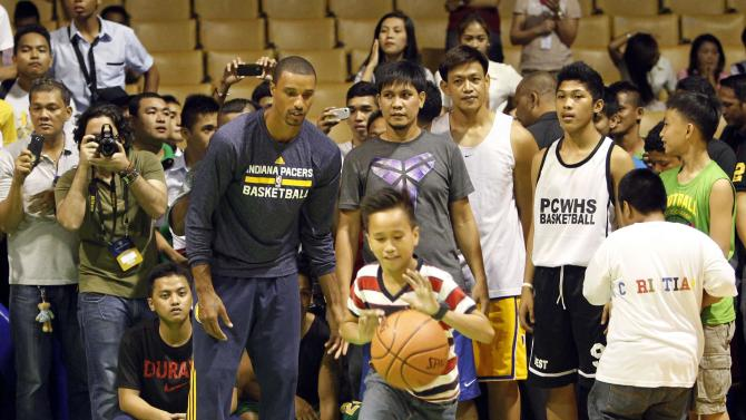 Indiana Pacers NBA George Hill watch a boy dribbling a ball during a basketball clinic in Pasay city