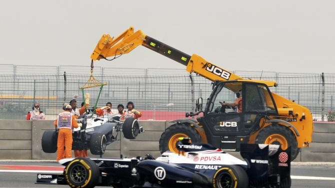 Williams Formula One driver Bottas drives past as the car of Williams Formula One driver Maldonado is lifted during the second practice session of the Indian F1 Grand Prix at the Buddh International Circuit in Greater Noida