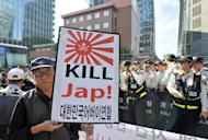 A protester holds a placard during an anti-Japanese rally over South Korean comfort women, outside the Japanese embassy in Seoul, on September 24, 2012. Up to 200,000 women from Korea, China, the Philippines and elsewhere were forcibly drafted into brothels catering to the Japanese military in territories occupied by Japan during WWII, according to many mainstream historians