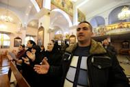 Syrians from the Christian town of Maalula attend a mass service at Saint Joseph's church on December 18, 2013 in Damascus