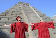 Students celebrate their graduation in front of a replica Mayan pyramid before a countdown by Taiwan's National Museum of Natural Science to help reassure the public it is not the end of the world, in Taichung on December 21, 2012. A global day of lighthearted doom-themed celebration culminated Friday in the jungle temples of the Mayan people of Central America, whose calendar sparks apocalypse fears.
