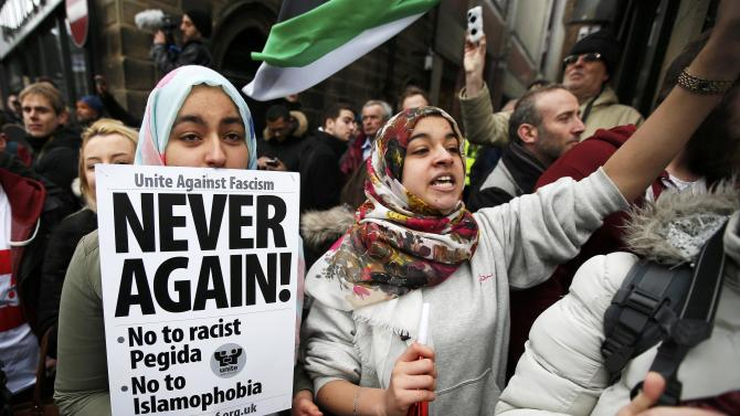 A girl holds a placard as she takes part in a counter-demonstrations against a rally by supporters of the Pegida movement in Newcastle, northern England