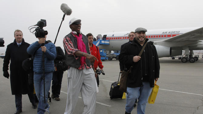 Former NBA basketball star Dennis Rodman, third left, and his entourage arrive at the international airport in Pyongyang, North Korea, Monday, Jan. 6, 2014. Rodman took a team of former NBA players on a trip for an exhibition game on Kim Jong Un's birthday, Wednesday, Jan. 8. (AP Photo/Kim Kwang Hyon)