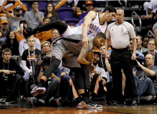 Phoenix Suns' Markeiff Morris is fouled by Oklahoma City Thunder forward Enes Kanter, rear, of Turkey, during the second half of an NBA basketball game, Thursday, Feb. 26, 2015, in Phoenix. The Su