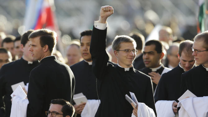A young priest punches the air as he reaches his seat in Vatican square for the inauguration of Pope Francis in St. Peter's Square at the Vatican, Tuesday, March 19, 2013. (AP Photo/Gregorio Borgia)