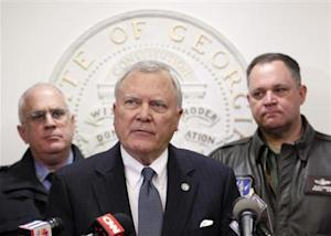 Georgia Governor Deal speaks to the media as Public Safety Director McDonough and Georgia National Guard Director Butterworth listen at the State Capitol in Atlanta