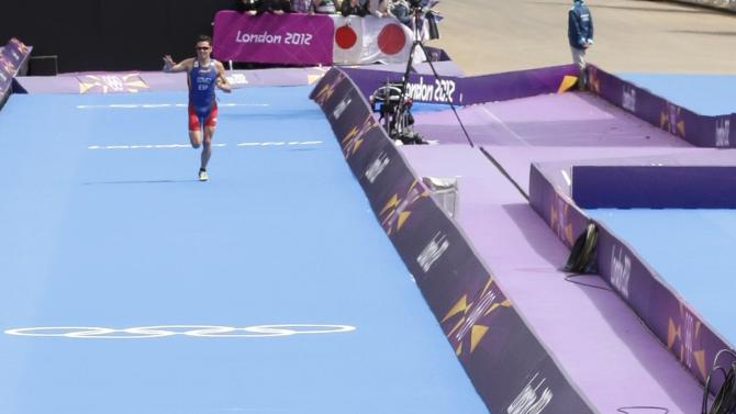 Britain's Alistair Brownlee looks back on finish line at Spain's Javier Gomez in the men's triathlon final during the London 2012 Olympic Games at Hyde Park