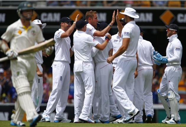 England's Broad celebrates with teammates after taking the wicket of Australia's Rogers during the third day's play of the first Ashes cricket test match in Brisbane
