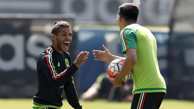 Mexico's soccer player Jonathan Dos Santos gestures to Hector Herrera during a soccer training session in Mexico City