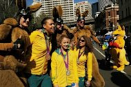 Australian Olympic athletes Elizabeth Cambage (L), Brittany Broben (C) and Jessica Fox pose with people dressed as bouncing kangaroo mascots during a welcome home street parade on August 20 in Sydney