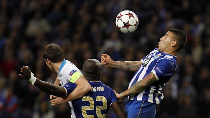 Porto's Nicolas Otamendi, right, from Argentina, and Eliaquim Mangala, from France, vies for a high ball with Zenit's captain Igor Smolnikov, left, during the Champions League group G soccer match between FC Porto and Zenit at the Dragao stadium in Porto, northern Portugal, Tuesday, Oct. 22, 2013. Zenit won 1-0