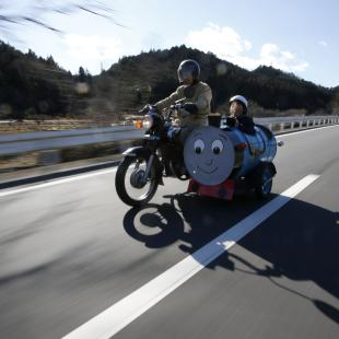 Sadao Kimbara rides on a Honda motorcycle with a sidecar he made out of an oil barrel as his grandson Rui smiles in the sidecar in Ome, outskirts of Tokyo