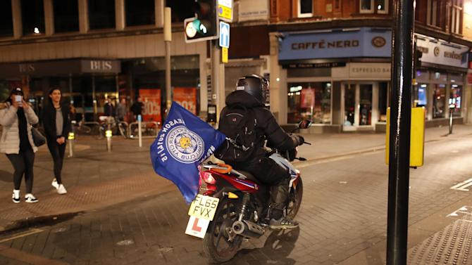 A Leicester City fan celebrates winning the Premier League with a flag on his motorbike