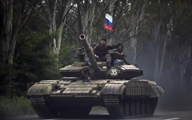Fotografía de archivo del 29 de julio de 2014de rebeldes prorrusos sobre un tanque con la bandera de Rusia en un camino del este de Donetsk, Ucrania. (Foto AP/Vadim Ghirda, Archivo)