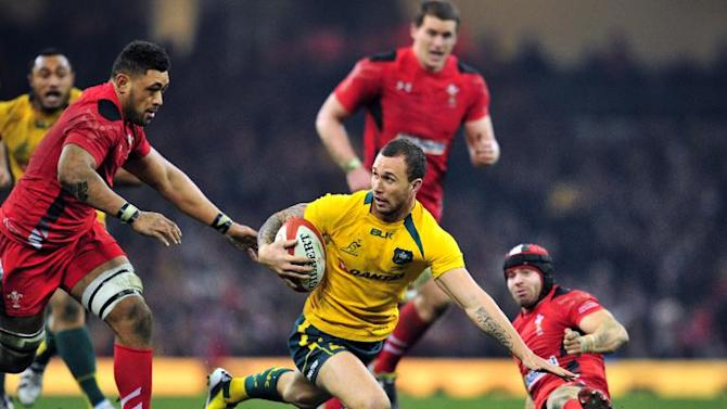Australia's fly-half Quade Cooper (C) evades Wales' No. 8 Toby Faletau (L) during their rugby union Test match at the Millennium Stadium in Cardiff, Wales, on November 30, 2013