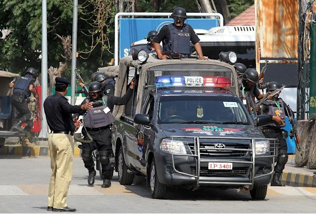 Pakistani police commandos stand alert as a bus carrying the Zimbabwe cricket team players arrives at the Gaddafi Stadium,  Saturday, May 23, 2015 for a practice session in Lahore, Pakistan. Zimbabwe