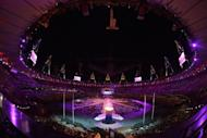 This picture shows a general view with the Olympic flame in the foreground during the closing ceremony of the 2012 London Olympic Games at the Olympic stadium in London